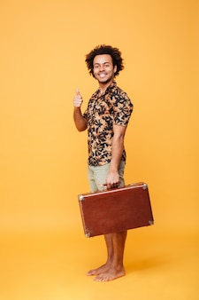 Happy young african man holding suitcase showing thumbs up.