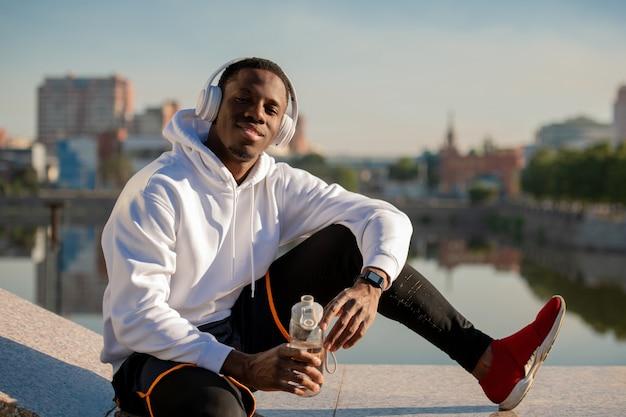 강변에 의해 대리석 타일에 앉아있는 동안 헤드폰과 운동복에 행복 한 젊은 아프리카 남자 야외 훈련 후 음료를 데