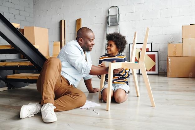 両方が床に座っている間彼に木製の椅子を組み立てる方法を教えている間彼のかわいい幼い息子を見ている幸せな若いアフリカ人