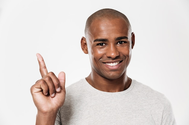 Happy young african man pointing.