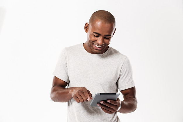 Happy young african man using tablet computer.