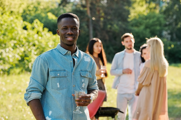 Happy young african man with glass of white wine with friends cooking barbecue and talking