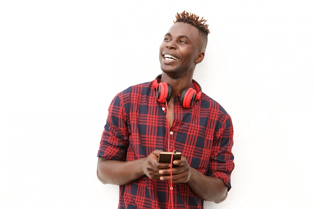 Happy young african man with headphones and mobile phone