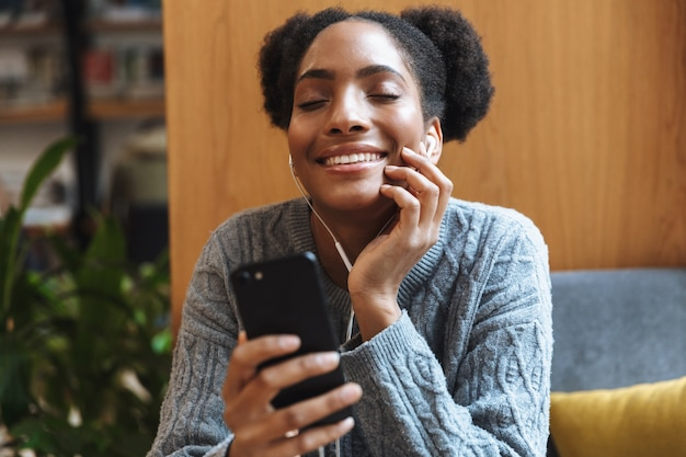 Счастливый молодой африканский студент девушка учится в библиотеке, слушая музыку в наушниках