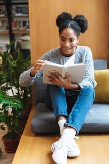 図書館で勉強し、本を読んで幸せな若いアフリカの学生の女の子