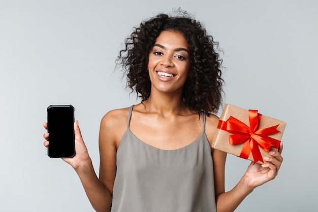 Happy young african woman casually dressed standing isolated, holding blank screen mobile phone, showing gift box
