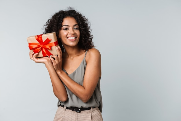Happy young african woman casually dressed standing isolated, holding a gift box