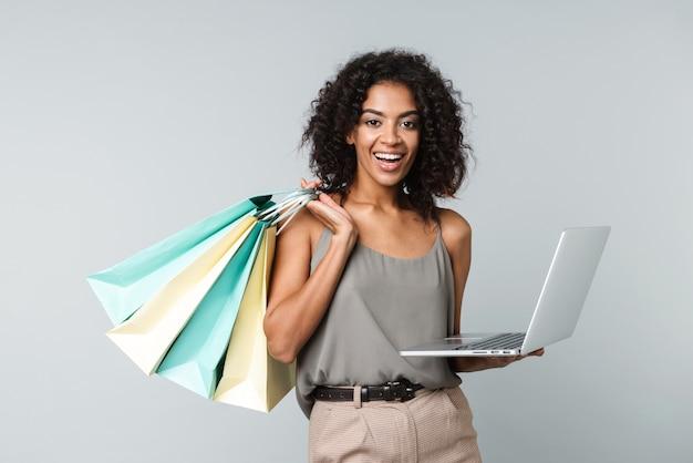 Счастливая молодая африканская женщина, небрежно одетая, стоя изолированно, держа портативный компьютер, неся сумки для покупок