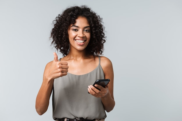 Happy young african woman casually dressed standing isolated, holding mobile phone, thumbs up