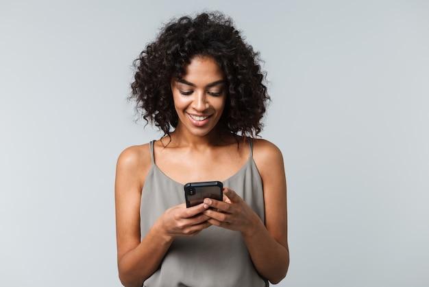 幸せな若いアフリカの女性は、携帯電話を持って、孤立して立ってカジュアルな服を着ています