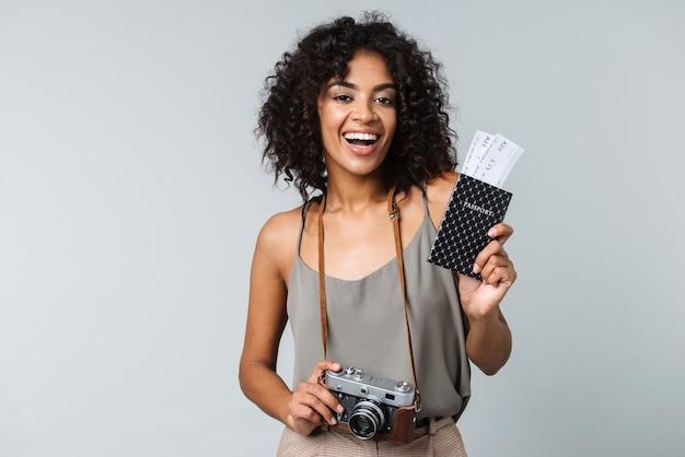 Счастливая молодая африканская женщина, небрежно одетая, стоя изолированно, держа фотоаппарат, показывая паспорт с билетами на самолет
