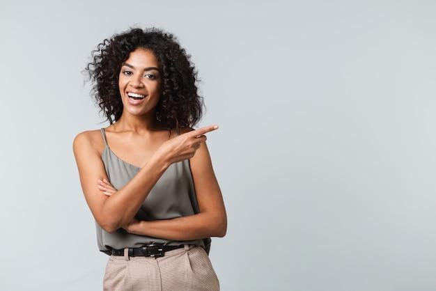행복 한 젊은 아프리카 여자 부담없이 고립 된 서 옷을 입고 멀리 가리키는