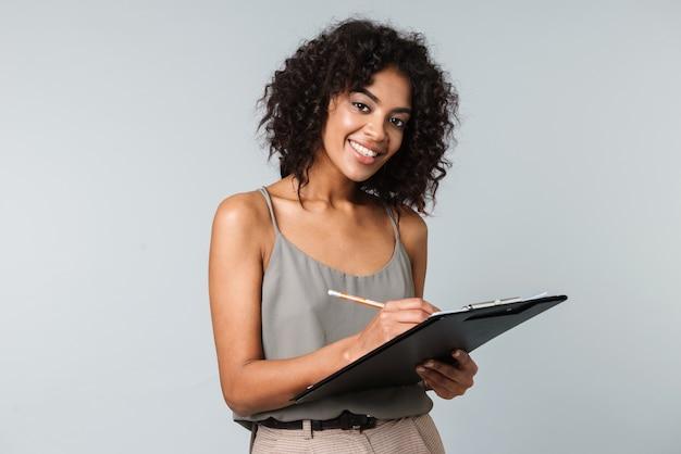 幸せな若いアフリカの女性は、メモ帳でメモを取る、孤立して立ってカジュアルな服を着て