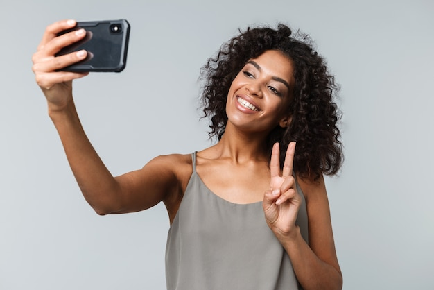 Happy young african woman casually dressed standing isolated, taking a selfie