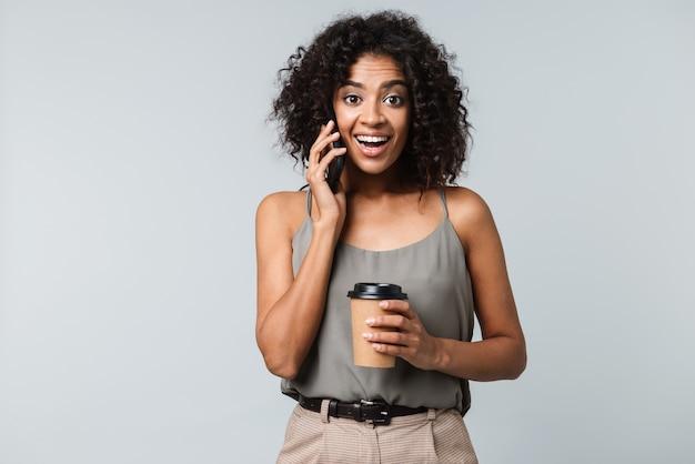 Счастливая молодая африканская женщина, небрежно одетая, стоя изолированно, разговаривает по мобильному телефону, держа чашку кофе на вынос