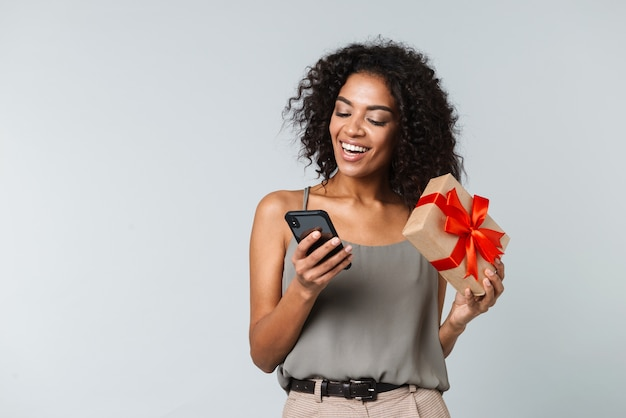 Happy young african woman casually dressed standing isolated, using mobile phone, showing gift box