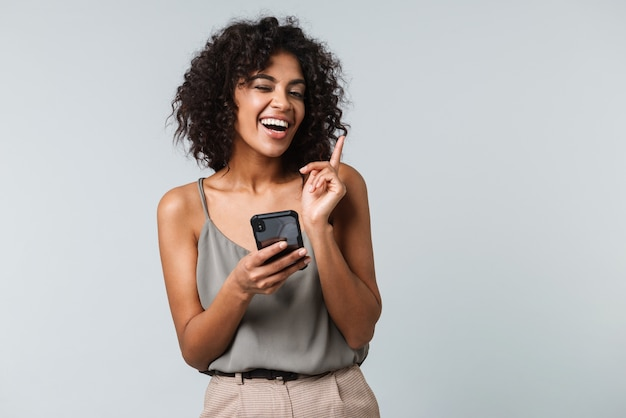 Happy young african woman casually dressed standing isolated, using mobile phone