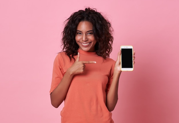 Happy young african woman hand pointing at blank screen mobile phone on pink background