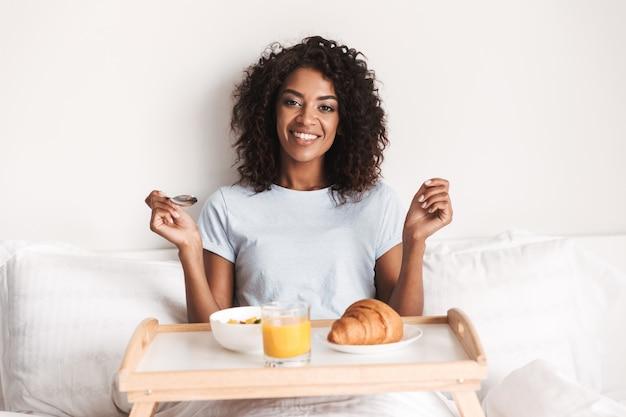 おいしい朝食を持っている幸せな若いアフリカの女性