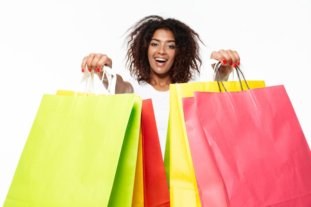 Happy young african woman holding shopping bags.