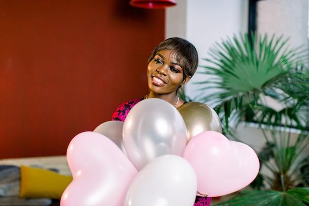 Счастливая молодая африканская женщина в платье с воздушными шарами в ее руках.