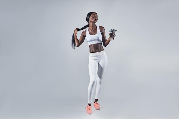 물병을 들고 머리를 조절하는 스포츠 의류를 입은 행복한 젊은 아프리카 여성