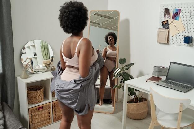 鏡で見ている下着で幸せな若いアフリカの女性