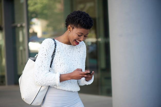 휴대 전화에서 텍스트를 읽고 행복 한 젊은 아프리카 여자