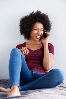 Happy young african woman relaxing and talking on mobile phone