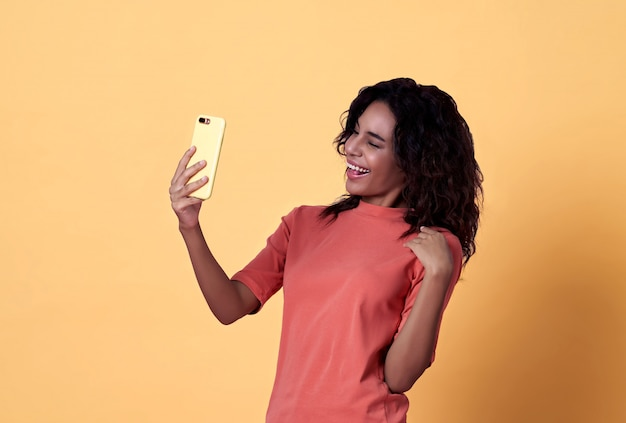 Happy young african woman selfie celebrating with mobile phone over yellow background