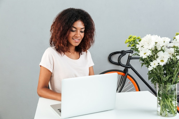 Happy young african woman sitting over grey wall using laptop