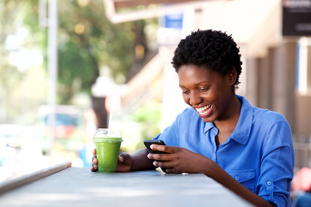 Happy young african woman sitting at outdoor cafe using mobile phone