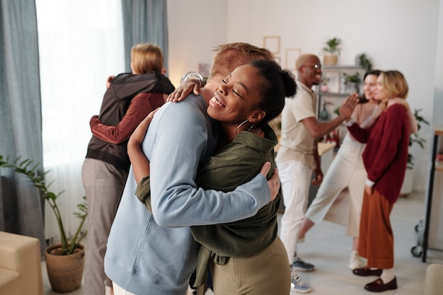 Happy young african woman in smart casualwear giving hug to guy in blue pullover in front of camera against their friends embracing and talking