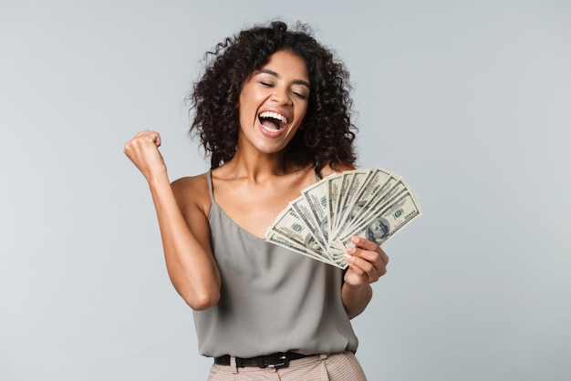 Happy young african woman standing isolated, holding bunch of money banknotes, celebrating