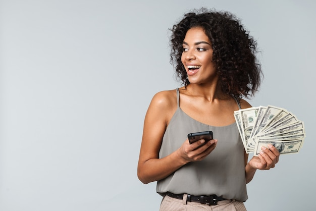 Happy young african woman standing isolated, holding bunch of money banknotes, using mobile phone