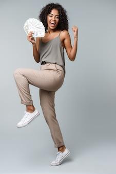 Счастливая молодая африканская женщина, стоящая изолированно, держа кучу денежных банкнот, празднуя