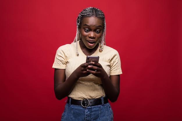 Счастливая молодая африканская женщина пользуется мобильным телефоном, небрежно одетым, стоя изолированным на красном фоне