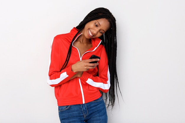 Happy young african woman using mobile phone against white background
