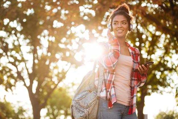 公園で野外を歩いている幸せな若いアフリカ人女性