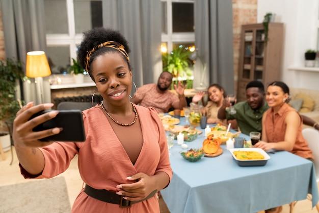 Счастливая молодая африканская женщина со смартфоном, делающая селфи перед камерой против мужчины, мальчика-подростка и девочек, сидящих за праздничным столом