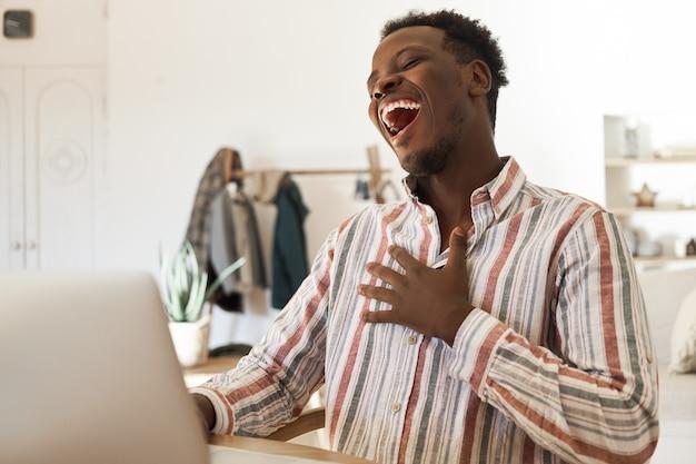 幸せな若いアフリカ系アメリカ人の男性がビデオ通話をして、笑って、機嫌が良い友達とチャットしています。
