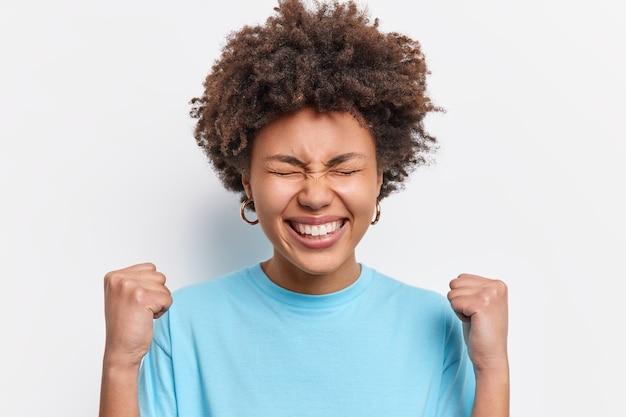 Счастливая молодая афро-американка сжимает кулаки, празднует триумф победы от успеха, широко улыбается, на лице его обрадованное выражение, носит повседневную синюю футболку, изолированную над белой стеной. я выигрываю