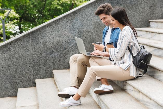Счастливые молодые удивительные любящие пары деловых людей коллеги на открытом воздухе снаружи на шагах, используя портативный компьютер, пить кофе.