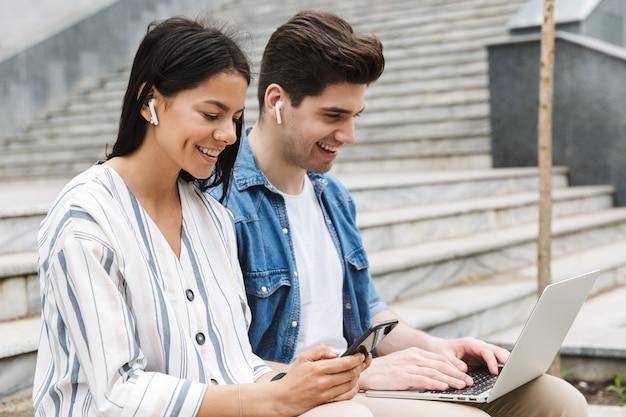 야외에서 휴대폰과 노트북 컴퓨터를 사용하여 이어폰으로 음악을 듣는 행복한 젊은 부부 사업가 동료들.