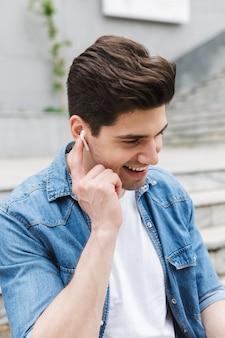 야외에서 이어폰으로 음악을 들으며 포즈를 취한 행복한 젊은 남자 사업가.