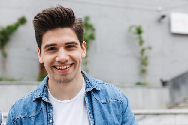 外で屋外でポーズをとって幸せな若い驚くべき男の実業家。