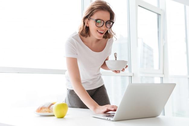 Счастливая молодая удивительная женщина печатая на портативном компьютере.