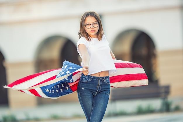 미국 국기를 들고 도시에서 손을 흔드는 행복한 젊은 미국 여학생.