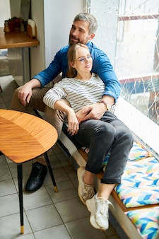 Счастливая молодая влюбленная пара в повседневной одежде отдыхает у окна в уютном кафе, наслаждаясь романтическим свиданием