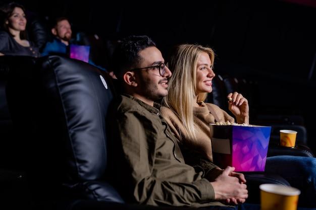 Счастливая молодая влюбленная пара расслабляется в кино перед большим экраном, наслаждаясь фильмом о любви